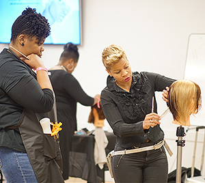Evie Johnson instructs a young stylist.   (Photos: Urban News Service)
